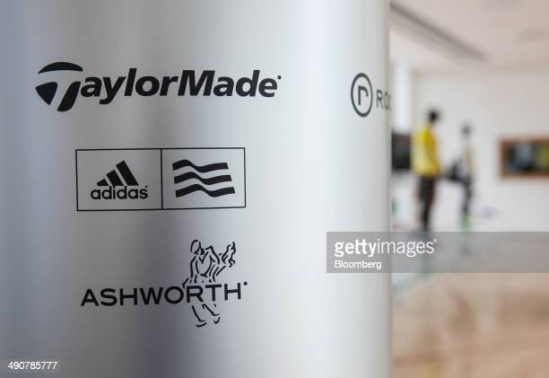 The TaylorMadeAdidas golf business logo sits on a sign above the Adidas and Ashworth golfing apparel brand logos in the reception area of Adidas AG's...