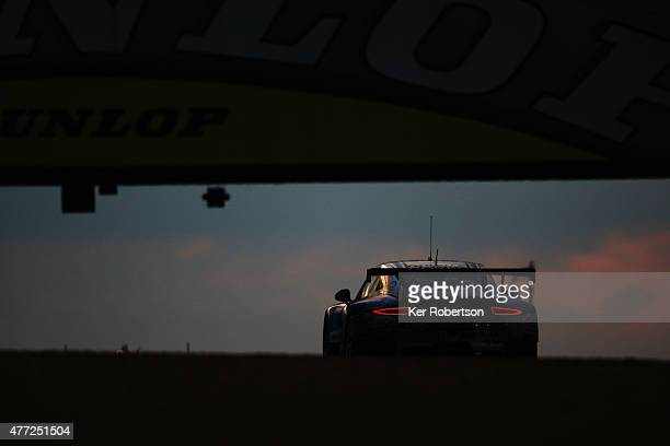 The Team AAI Porsche 911 of HanChen Chen Gilles Vannelet and Mike Parisy drives under the Dunlop Bridge at dawn during the Le Mans 24 Hour race at...