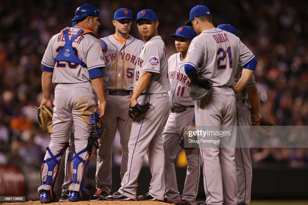 The team gathers around relief pitcher Daisuke Matsuzaka #16 of the New York Mets as he works against the Colorado Rockies in the seventh inning at Coors Field on May 3, 2014 in Denver, Colorado. The Rockies defeated the Mets 11-10.