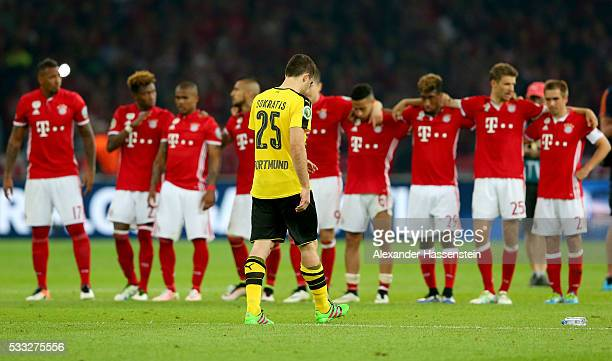 The team of Bayern Muenchen reacts during the DFB Cup Final penalty shootout whilst Sokratis Papastatopoulos is dejected between Bayern Muenchen and...