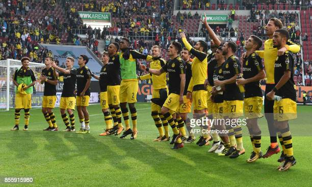 The team of Borussia Dortmund celebrate in front of the supporters after the German first division Bundesliga football match between FC Augsburg and...
