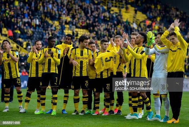 The team of Borussia Dortmund celebrates the win after the final whistle with the shirt of their missing Dortmund's Spanish defender Marc Bartra who...