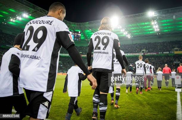 The Team of Borussia Moenchengladbach walks in the BORUSSIAPARK with the name of its injured teammate Mamadou Doucoure on the jersey prior the...