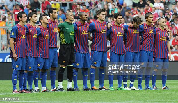 The team of FC Barcelona observes a minute of silence in remembrance of the victims of the Oslo attacks ahead of their Audi Cup football match FC...