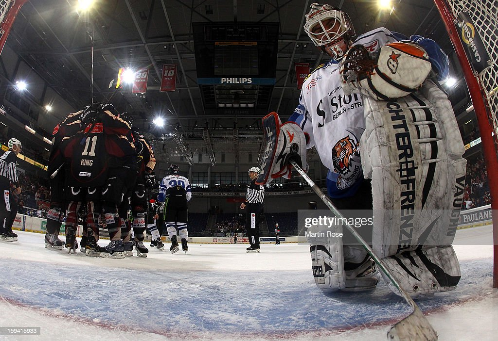 The team of Hannover (L) celebrate their 4th goal while Jason Bacashihua (R), goaltender of Straubing looks dejected during the DEL match between Hannover Scorpions and Straubing Tigers at TUI Arena on January 13, 2013 in Hanover, Germany.