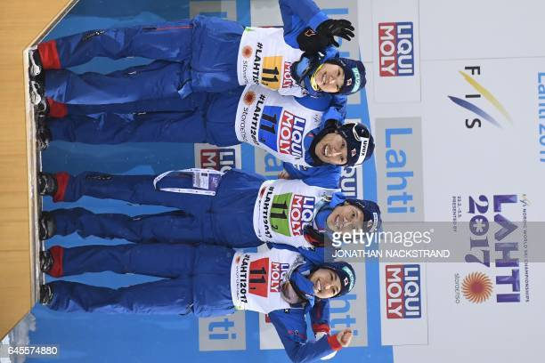 The team of Japan Yuki Ito Daiki Ito Taku Takeuchi and Sara Takanashi celebrate during the flower ceremony after the ski jumping mixed normal hill...