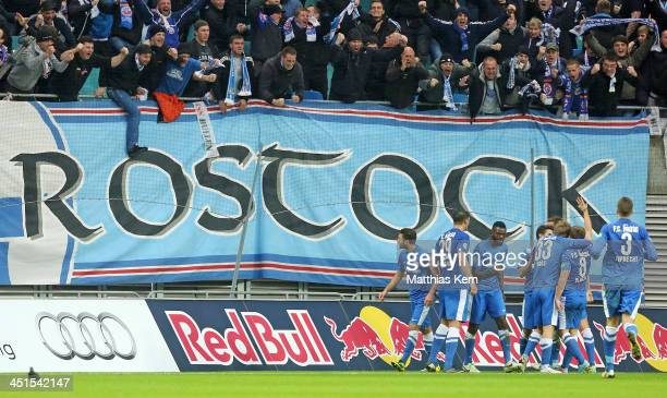The team of Rostock celebrate with their supporters after David Blacha scores the first goal during the third league match between RB Leipzig and FC...