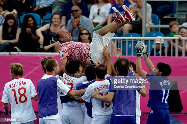 The team of Russia celebrate with head coach Avtandil Baramidze after winning the gold in the Men's Team Football 7aside Gold Medal match against...