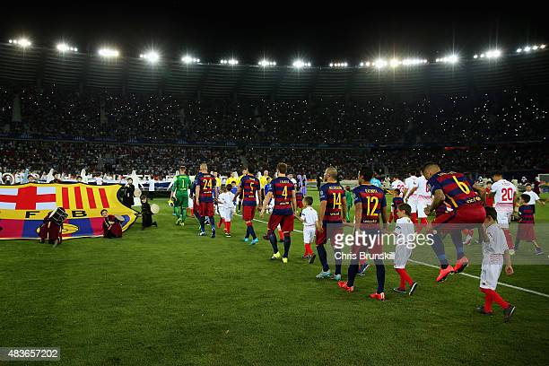 The teams head out during the UEFA Super Cup between Barcelona and Sevilla FC at Dinamo Arena on August 11 2015 in Tbilisi Georgia