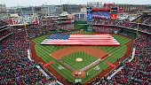 The teams line the base paths as the National Anthem is sung before the Opening Day game at Nationals Park between the Washington Nationals and the...