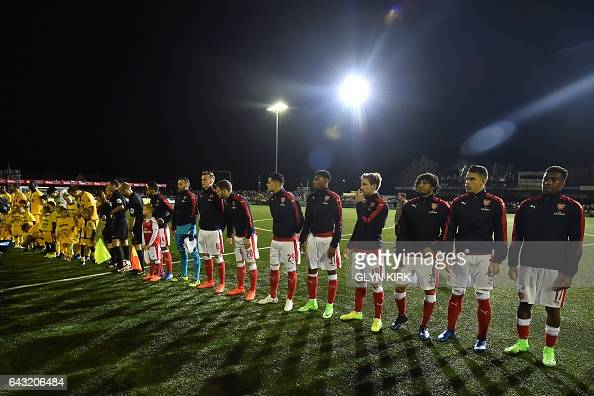 The teams line up ahead of the English FA Cup fifth round football match between Sutton United and Arsenal at the Borough Sports Ground Gander Green...