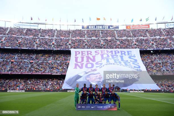 The teams line up as a banner is shown in tribute to Luis Enrique Manager of Barcelona during the La Liga match between Barcelona and Eibar at Camp...