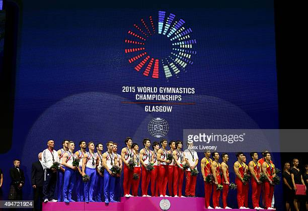 The teams of Great Britain Japan and China stand for the national anthem during day six of the 2015 World Artistic Gymnastics Championships at The...