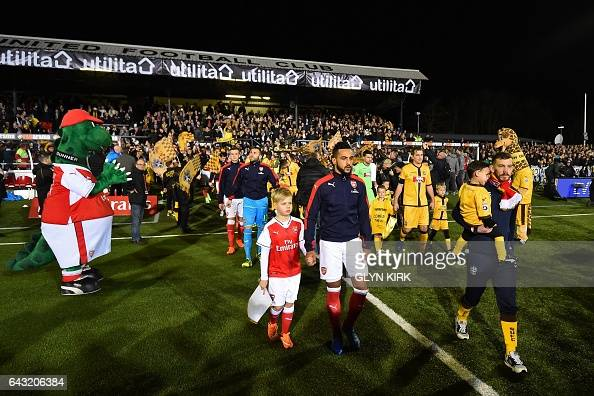 The teams walk out ahead of the English FA Cup fifth round football match between Sutton United and Arsenal at the Borough Sports Ground Gander Green...