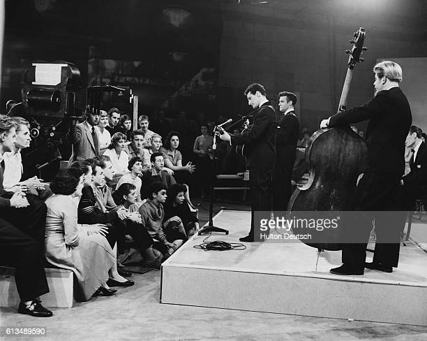 The teenage audience claps along to the music of Lonnie Donegan and his skiffle group during the recording of the film Six five Special at the...
