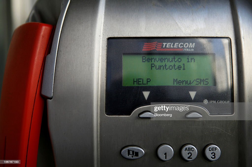 The Telecom Italia SpA logo sits above the digital display of a payphone in Milan, Italy, on Tuesday, Nov. 20, 2012. Telecom Italia SpA said it is still reviewing the possible spinoff of its fixed-line network and the company's board will discuss the outcome of its analysis on Dec. 6. Photographer: Alessia Pierdomenico/Bloomberg via Getty Images