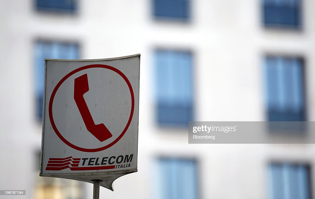The Telecom Italia SpA logo sits on a sign indentifying the location of public pay-telephones in Milan, Italy, on Tuesday, Nov. 20, 2012. Telecom Italia SpA said it is still reviewing the possible spinoff of its fixed-line network and the company's board will discuss the outcome of its analysis on Dec. 6. Photographer: Alessia Pierdomenico/Bloomberg via Getty Images