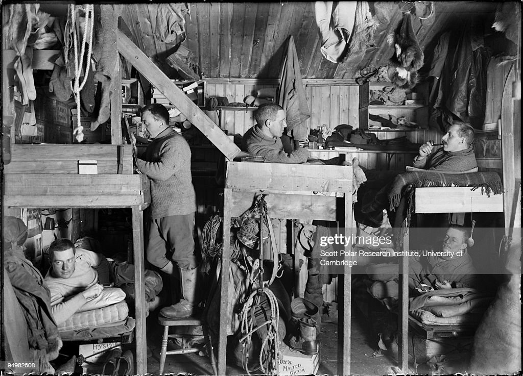 'The Tenements' - bunkbeds in a Winter Quarters hut on the Ross Dependency, during Captain Robert Falcon Scott's Terra Nova Expedition to the Antarctic, 9th October 1911. Henry Robertson Bowers, Lawrence Oates, Cecil Meares and Edward L. Atkinson lie on bunks, while Apsley Cherry-Garrard stands on the left.