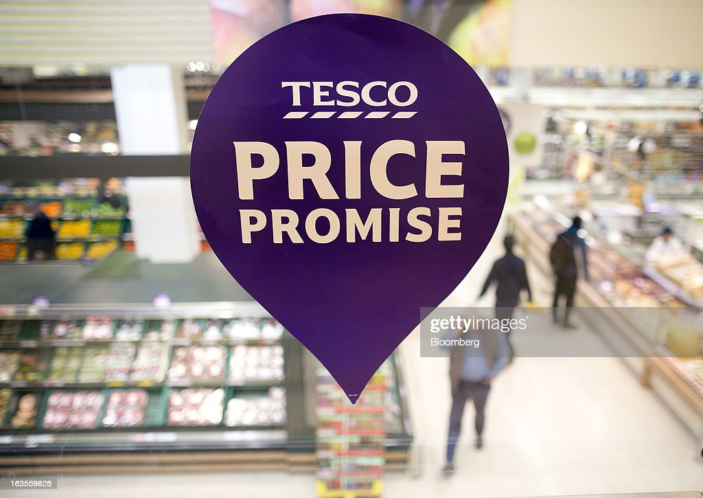 The Tesco 'Price Promise' logo is displayed on a glass wall above the main shopping floor inside a Tesco Plc supermarket in the borough of Kensington in London, U.K., on Tuesday, March 12, 2013. Tesco Plc, the U.K.'s largest grocer launched a 'Price Promise', its latest initiative offering to match the price of customers' purchases to that of it's rivals, including Wal-Mart Stores Inc.'s ASDA. Photographer: Simon Dawson/Bloomberg via Getty Images