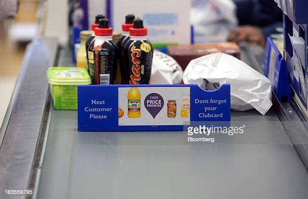 The Tesco 'Price Promise' logo sits on conveyor belt at the checkout counter inside a Tesco Plc supermarket in the borough of Kensington in London UK...