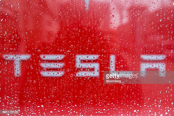 The Tesla logo is seen beyond droplets of rain water as they sit on the window of a Tesla Motors Inc electric automobile showroom in Berlin Germany...