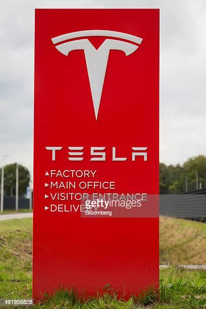 The Tesla logo sits on a sign outside the Tesla Motors Inc factory in Tilburg Netherlands on Thursday Oct 8 2015 Tesla said it delivered 11580...