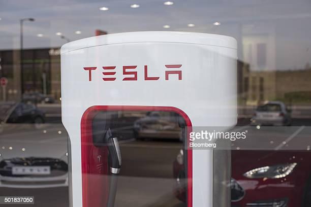 The Tesla logo sits on an electric automobile charging station inside a Tesla Motors Inc showroom in Paris France on Thursday Dec 17 2015 After...
