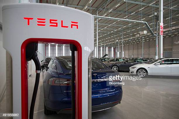 The Tesla logo sits on an electric charging station as new Tesla Model S automobiles stand in a delivery area ahead of European shipping following...