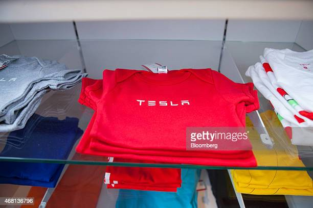 The Tesla logo sits tshirts and apparel display inside the Tesla Motors Inc store in Munich Germany on Monday March 30 2015 Chief Executive Officer...