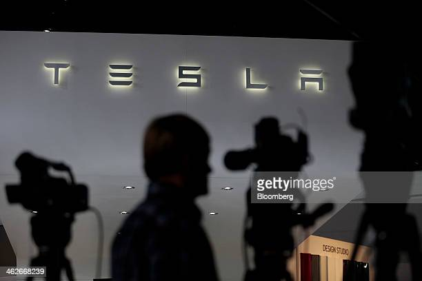 The Tesla Motors Inc logo is seen as the silhouettes of members of the media arrive at the company's booth during the 2014 North American...