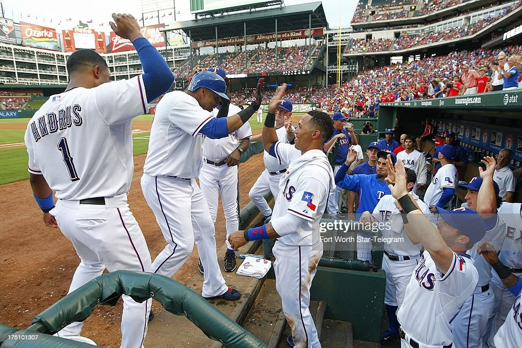The Texas Rangers' Nelson Cruz is greeted at the dugout steps after his second-inning home run against the Los Angeles Angels at the Rangers Ballpark in Arlington on Wednesday July 31, 2013, in Arlington, Texas.
