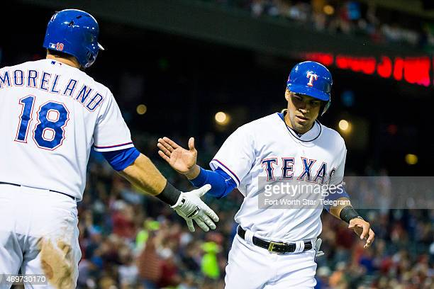 The Texas Rangers' Robinson Chirinos right celebrates with teammate Mitch Moreland after scoring during the second inning against the Los Angeles...