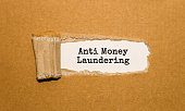 The text Anti Money Laundering appearing behind torn brown paper