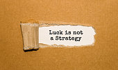 The text Luck is not A Strategy appearing behind torn brown paper