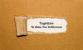 The text Together We Make The Difference appearing behind torn brown paper