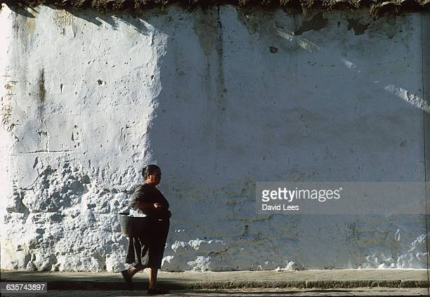 The texture of a whitewashed wall is highlighted by the shadows cast across it