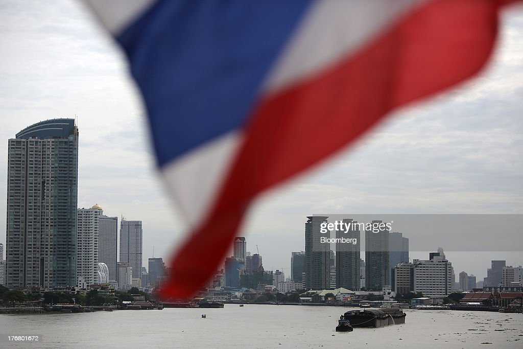 The Thai national flag flies on the Krungthep Bridge as a barge is pulled along the Chao Praya river in Bangkok, Thailand, on Sunday, Aug. 18, 2013. Thai economic growth slowed for a second quarter as exports cooled and local demand weakened, with rising household debt restricting the scope for monetary easing. Photographer: Dario Pignatelli/Bloomberg via Getty Images