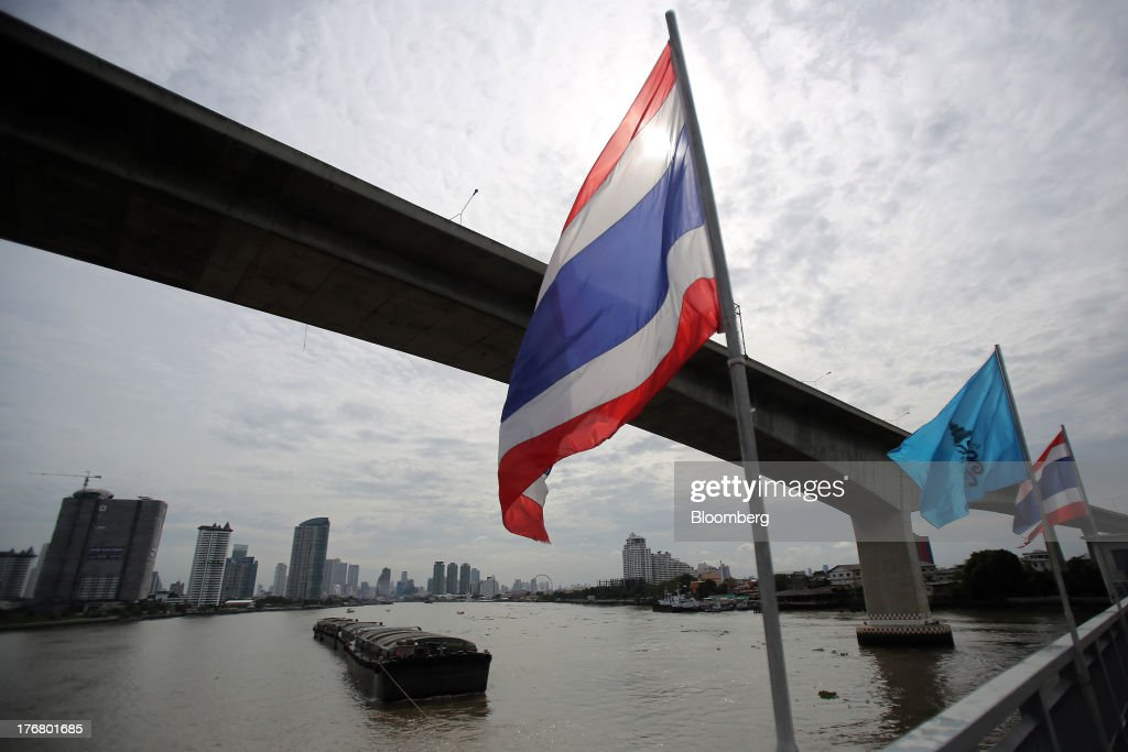 The Thai national flag flies on the Krungthep Bridge as a barge is pulled under the Rama III Bridge on the Chao Praya river in Bangkok, Thailand, on Sunday, Aug. 18, 2013. Thai economic growth slowed for a second quarter as exports cooled and local demand weakened, with rising household debt restricting the scope for monetary easing. Photographer: Dario Pignatelli/Bloomberg via Getty Images