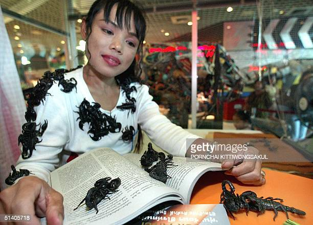 The 'Thai Scorpion Queen' Kanchana Ketkeaw reads a magazine with scorpions as she sets out for a new Guinness World Record for 'the longest stay with...
