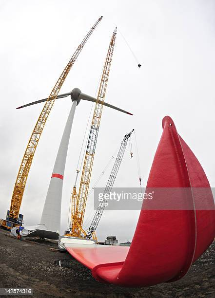 The third blade of a wind turbine lays on the ground beneath a partially completed unit at the Estinnes wind turbine park in Bray on February 5 2009...