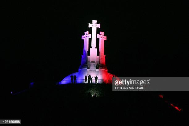 The three Crosses monument is illuminated in French national colors in Vilnius on November 14 2015 a day after a series of terror attacks in the...
