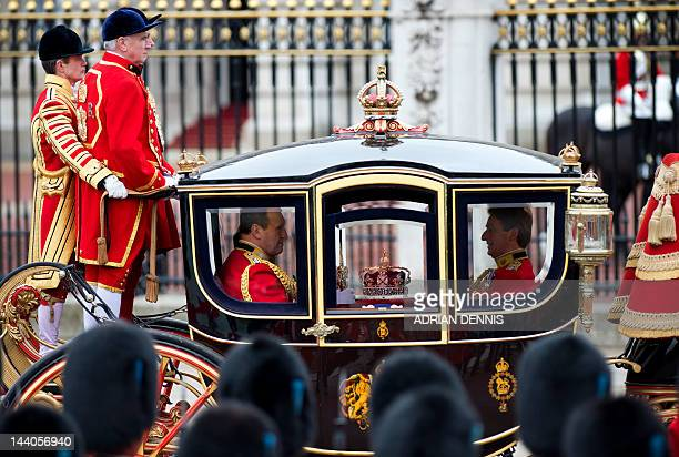 The three symbols of sovereign power the Imperial State Crown the Sword of State and the Cap travel in Queen Alexandra's State Coach returning to...