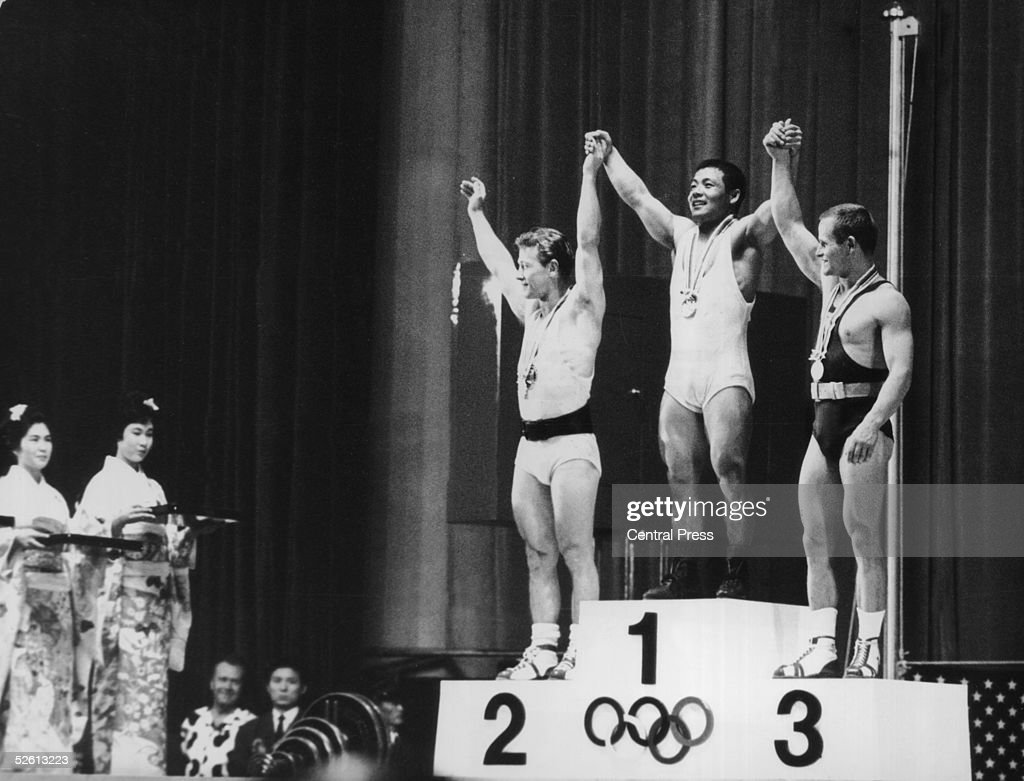The three winners of the Featherweight Weightlifting event at the Tokyo Olympics, 14th October 1964. From left to right, they are Isaac Berger of the US (silver), Yoshinobu Miyake of Japan (gold) and Mieczyslaw Nowak of Poland (bronze).