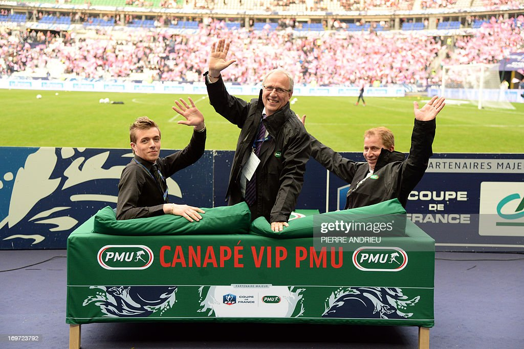 The three winners of the 'VIP sofa' contest organised by France's state-run bookmaker PMU wave as they sit on a sofa prior to watch from the pitch the French Cup final football match Bordeaux (FCGB) vs. Evian (ETGFC) on May 31, 2013 at the Stade de France stadium in Saint-Denis, outside Paris. The 'VIP sofa' contest was organised for the first time today as part of the French Cup football final by the PMU (Pari Mutuel Urbain), the French state-run betting system. AFP PHOTO / PIERRE ANDRIEU
