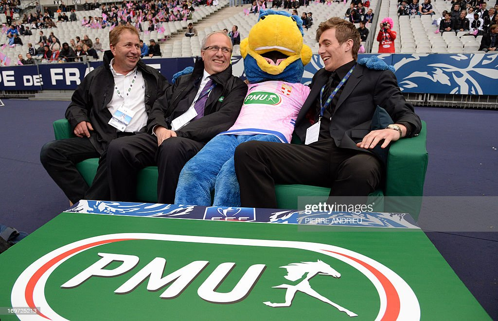 The three winners of the 'VIP sofa' contest organised by France's state-run bookmaker PMU pose with a mascot on a sofa prior to watch from the pitch the French Cup final football match Bordeaux (FCGB) vs. Evian (ETGFC) on May 31, 2013 at the Stade de France stadium in Saint-Denis, outside Paris. The 'VIP sofa' contest was organised for the first time today as part of the French Cup football final by the PMU (Pari Mutuel Urbain), the French state-run betting system.