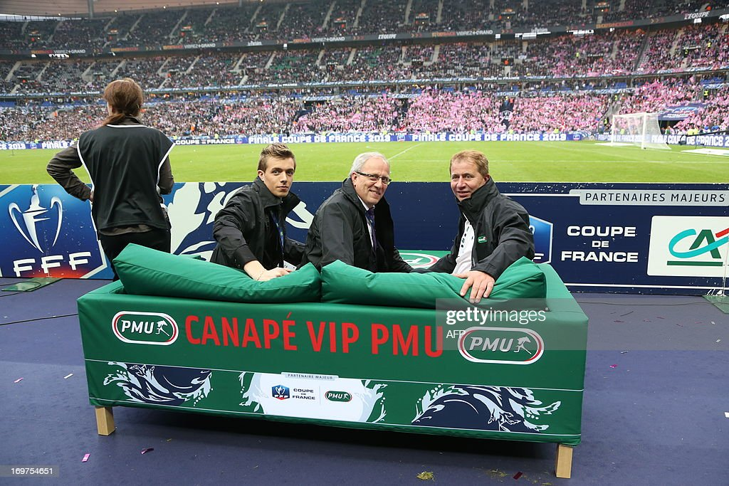 The three winners of the 'VIP sofa' contest organised by France's state-run bookmaker PMU pose on a sofa prior to watch from the pitch the French Cup final football match Bordeaux (FCGB) vs. Evian (ETGFC) on May 31, 2013 at the Stade de France stadium in Saint-Denis, outside Paris. The 'VIP sofa' contest was organised for the first time today as part of the French Cup football final by the PMU (Pari Mutuel Urbain), the French state-run betting system.