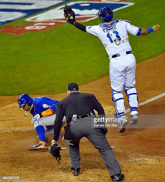 The throw from Kansas City Royals left fielder Alex Gordon is too late to catcher Salvador Perez allowing the New York Mets' Yoenis Cespedes left to...