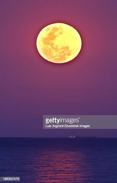 The Thunder's Moon and its reflection above the water of Rio de La Plata, Buenos Aires, Argentina.