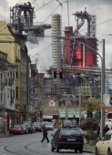 The ThyssenKrupp steelworks loom behind a busy neighborhood street on April 24 2012 in Duisburg Germany Duisburg and neighboring cities which are at...