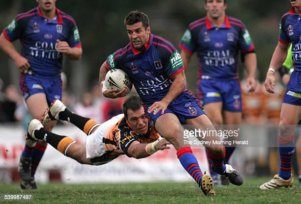 The Tigers' John Skandalis dives for the Knights' Brian Carney during the Round 10 NRL rugby league match between the Newcastle Knights and Wests...